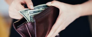 Woman holding an open wallet and thinking about unclaimed money