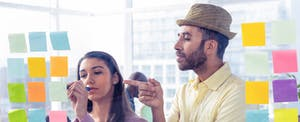 Man pointing at a Post-It note that a coworker is writing on full of little-known credit cards tips