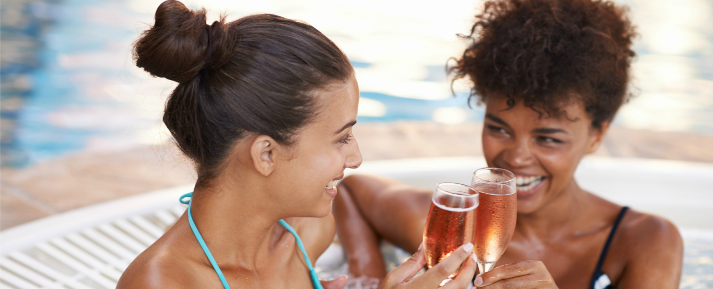 Two friends toasting eachother with prosecco in a hot tub because they've figured out how to maximize the benefits of the Platinum Card from American Express