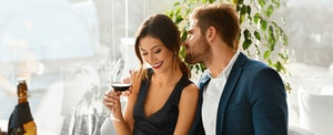 Young couple drinking wine in a fancy bar and maximizing the benefits of the Premier Rewards Gold Card from American Express