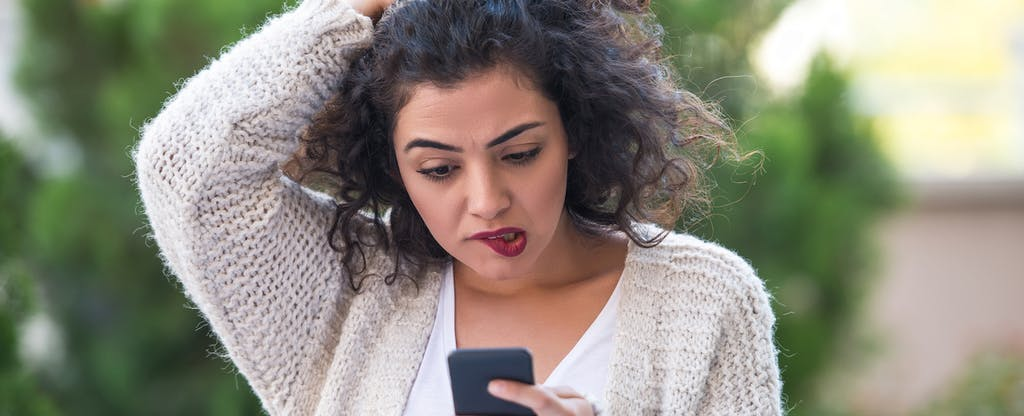 Concerned young woman looking at her phone to figure out what 5 things to do if you spot an unauthorized credit inquiry.