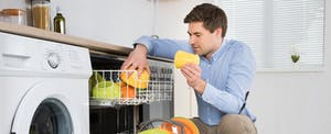 Man crouching to unload a dishwasher while wondering how to deal with delinquent accounts.