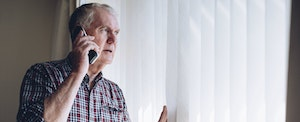 Senior man peering out the window and asking someone on the phone what to do if you're a victim of credit card fraud
