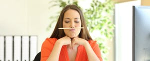 """Young woman balancing a pencil on her upper lip while wondering, """"Will a balance transfer hurt my credit score?"""""""