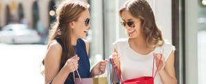 Two young women comparing shopping hauls and chatting about retail credit cards