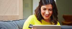 Smiling woman looking at a laptop with the best cash back credit cards for people with fair, good, and excellent credit