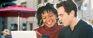 Young couple sitting outside and checking out the best credit card sign-up bonuses of 2017
