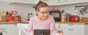 Woman sitting in her kitchen, looking at her credit card, and wondering how to avoid credit card fees