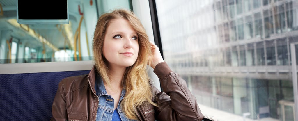 Young woman sitting on a bus and thinking about credit score ranges