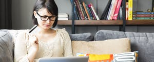 Woman on laptop explores how to lower credit card utilization rate