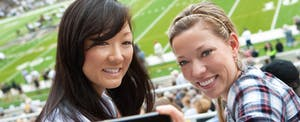 Two young women at an NFL game after using their NFL Extra Points Credit Card
