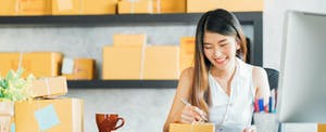 Woman addressing package, confident that she knows about business processing fees