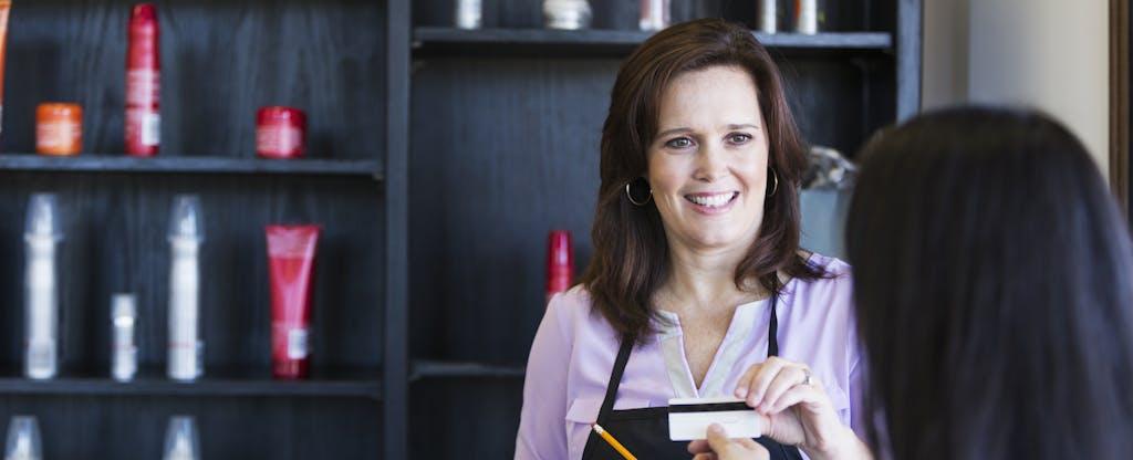Cafe owner handing over a secured business credit card