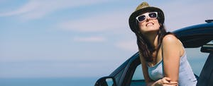 Young woman leaning out of her car window and thinking about whether or not it's worth it to refinance an auto loan
