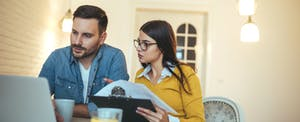 Couple analyzing bills realizing that household debt is on the rise in America
