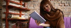 Young woman reading about balancing, saving, and paying debt