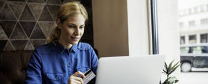 Woman using a Capital One secured Mastercard to shop online while building her credit