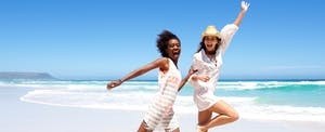 Two young woman on a beach vacation after learning about the Chase Sapphire Preferred benefits
