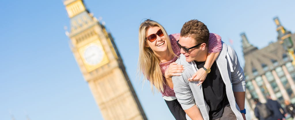 Young couple on vacation, fooling around in front of Big Ben after learning about the 9 airlines that offer companion tickets or discount codes