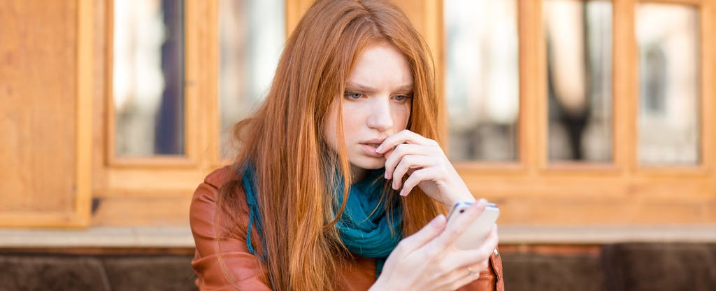 Woman looking at her phone with a concerned look while wondering how her credit card balances got so high and what she can do about it.