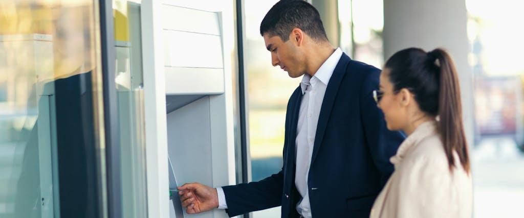 Man and woman are at an ATM debating credit vs debit vs cash