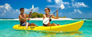 A couple kayaking in the Caribbean after maximizing their use of the Discover it® Miles card