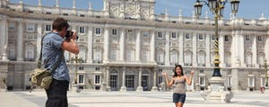 Tourists taking pictures at the Royal Palace Madrid, unconcerned about foreign transaction fees