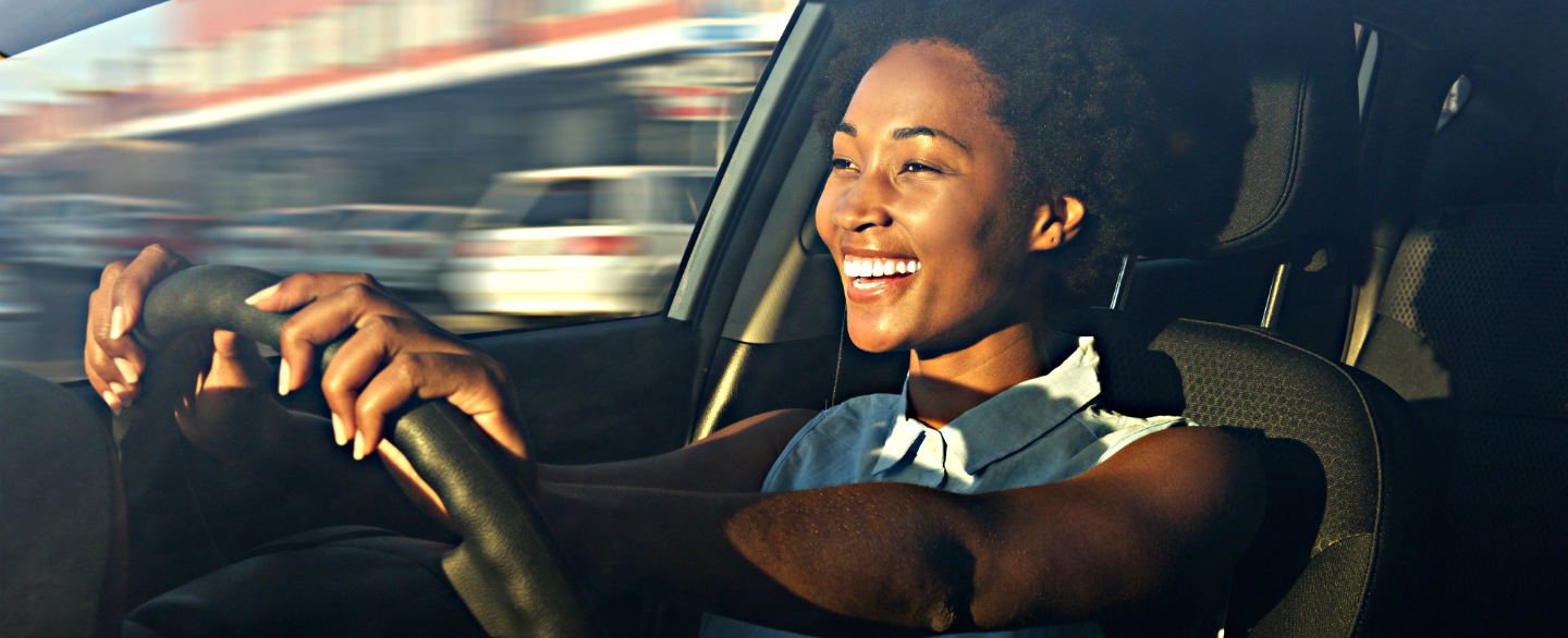 Smiling Woman Driving A Car And Wondering How Often To Shop For Car Insurance