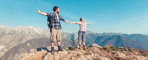Man and woman holding hands on top of a mountain, confident in their ability to pay abroad.