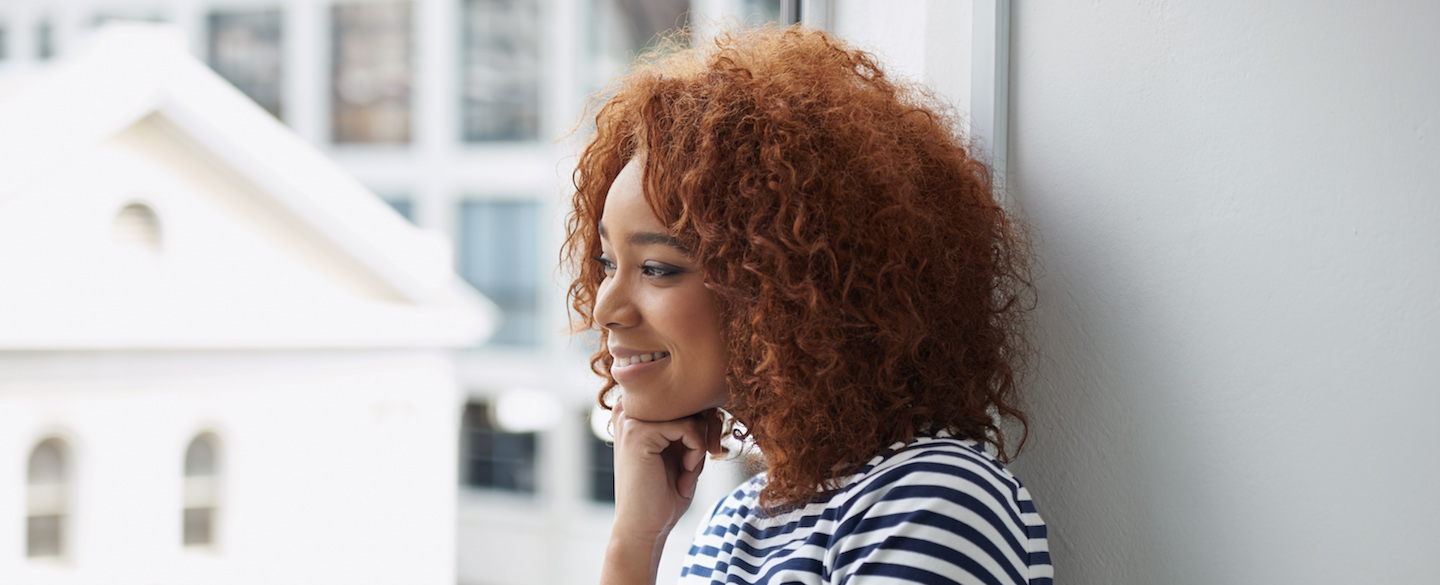Young woman sitting near a window learns 5 quick tips to improve your credit health
