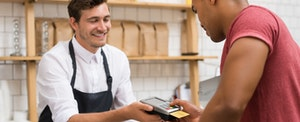 Customer pays for food purchase at with credit card.