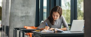 Young woman studying in a library after learning how to get a credit score.