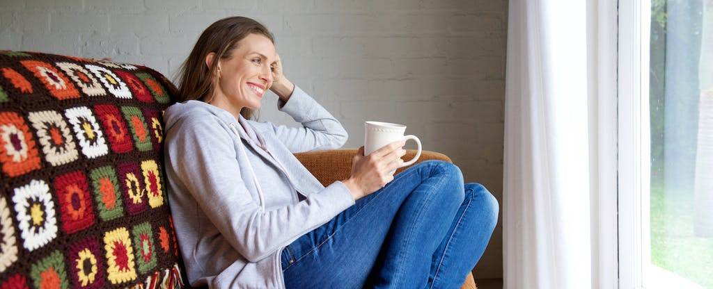 Woman sitting on a cozy couch, drinking coffee, and thinking about how to pay off debt by cutting her expenses