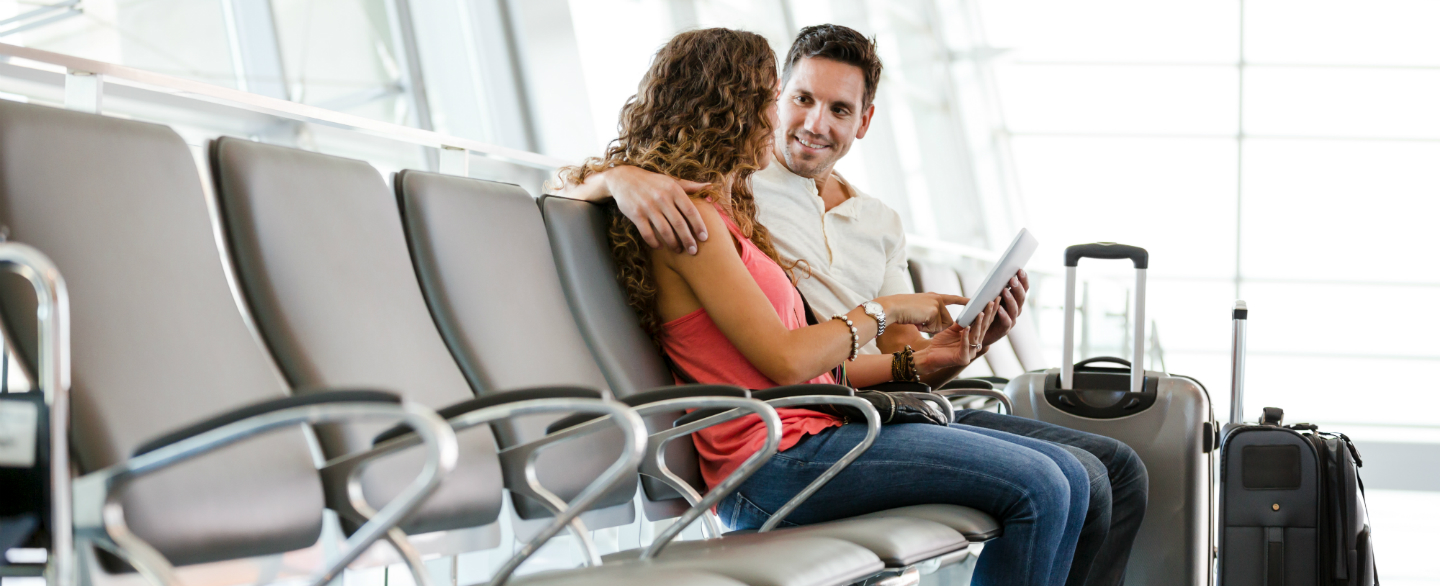 Couple at airport discussing the American Airlines AAdvantage program card.