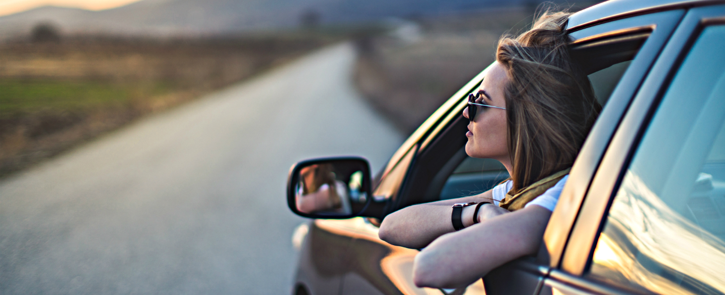 A woman in a car at sunset contemplates her potential auto refinancing savings
