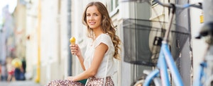 Young woman with her bike stops during her travels to enjoy an ice cream cone, thinking about all the travel rewards she's earning with her Bank of America travel rewards credit card.
