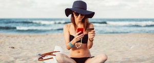 Woman on vacation at the beach shopping online with her Bank of America Rewards Travel Card