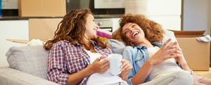 Two women laugh on the sofa in their new house after getting their debt-to-income ratio increase.