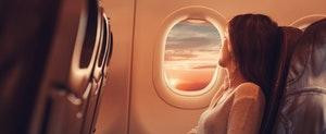 Woman in airplane looking through the window and contemplating if she should get the Gold Delta SkyMiles Credit Card or the Platinum Delta SkyMiles Credit Card