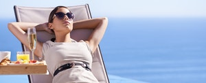 Sunbathing young woman enjoys the benefits of her Mastercard Black Card