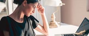 woman sitting at desk looking at laptop