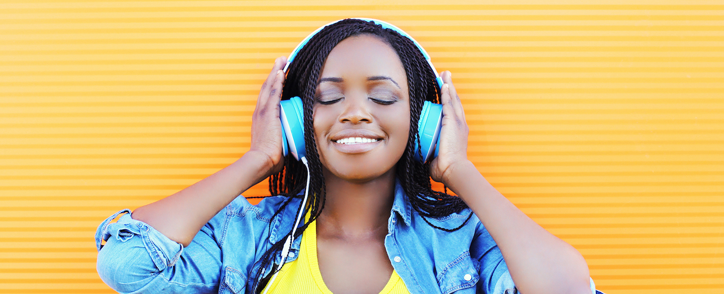 Smiling woman listens to headphones