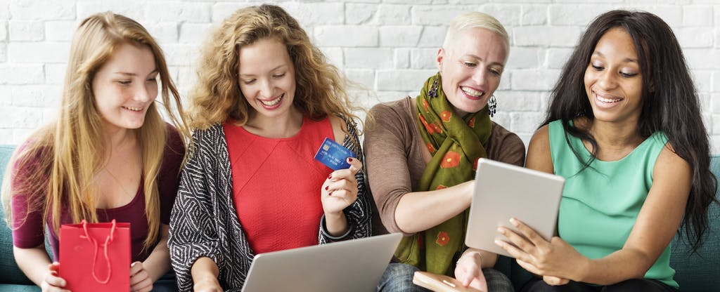 Group of women sitting on a couch and shopping online while comparing paypal credit cards