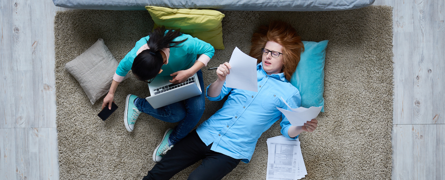 Young couple doing their taxes at home, deciding how to spend their tax refunds in a financially responsible way.