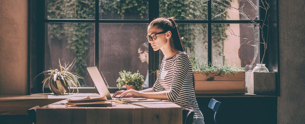 Young woman on laptop, learning about the three credit bureaus