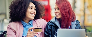 Two friends are shopping online with their new Total Visa credit card, an unsecured card for applicants with poor credit.