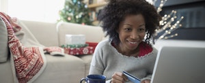 Smiling woman with credit card online shopping at her home decorated with holiday cheer, happy that she's using her credit card rewards to help her pay for gifts and avoid holiday debt
