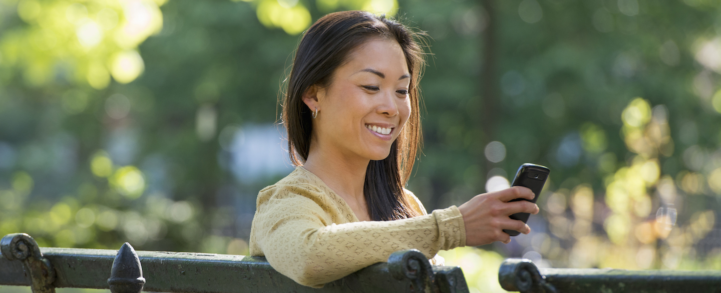 Smiling woman using Credit Karma Direct Dispute feature on her phone