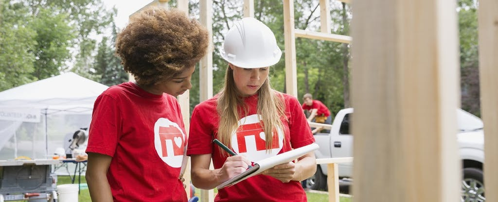 Two young women volunteers helping a charity build houses. Their charitable donations could net them a tax deduction.