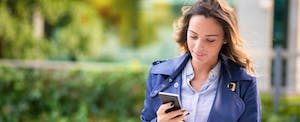 Young woman walking and checking her phone for reminders of important tax deadlines.